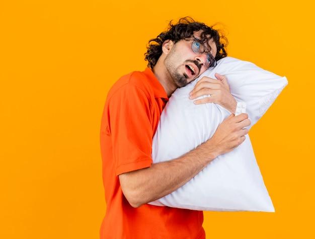 枕と医療用タブレットのパックを保持している眼鏡をかけている弱い若い白人の病気の人は、コピースペースでオレンジ色の背景にまっすぐに分離された枕に頭を置きます