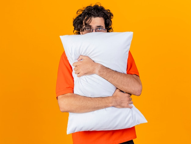 Debole giovane uomo malato caucasico con gli occhiali che abbraccia cuscino guardando la telecamera da dietro isolato su sfondo arancione con spazio di copia