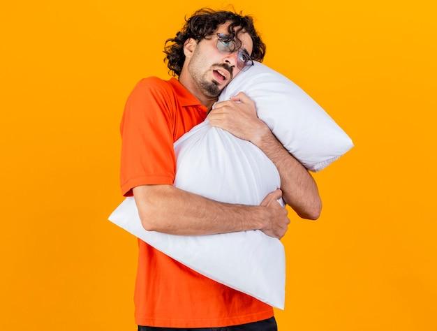Debole giovane indoeuropeo uomo malato con gli occhiali abbracciando cuscino cercando isolato su sfondo arancione con copia spazio