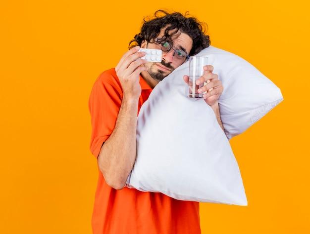 Debole giovane uomo malato caucasico con gli occhiali che abbraccia il cuscino che tocca il fronte con esso che tiene il pacchetto delle compresse mediche e del bicchiere d'acqua guardando le compresse isolate su fondo arancio con lo spazio della copia
