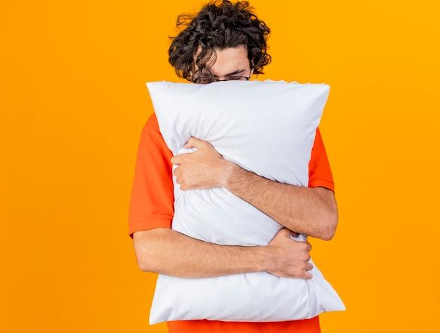 Debole giovane indoeuropeo uomo malato con gli occhiali che abbraccia cuscino con gli occhi chiusi isolato su sfondo arancione con copia spazio