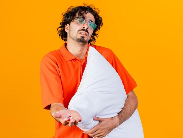 Debole giovane uomo malato caucasico con gli occhiali che guarda l'obbiettivo che tiene il cuscino che allunga le capsule mediche verso la macchina fotografica isolata su fondo arancio