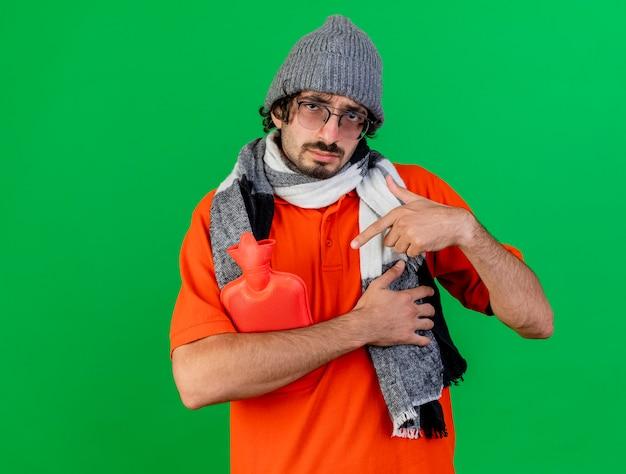 コピースペースで緑の背景に分離されたカメラを見て湯たんぽを保持し、指している眼鏡冬の帽子とスカーフを身に着けている弱い若い白人の病気の男