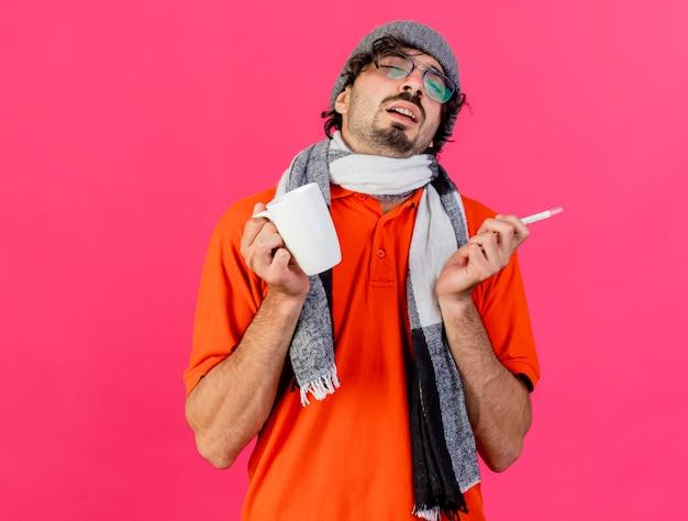 안경 겨울 모자와 스카프를 들고 약한 젊은 백인 아픈 남자가 복사 공간이 진홍색 배경에 고립 된 닫힌 눈으로 컵과 온도계를 들고