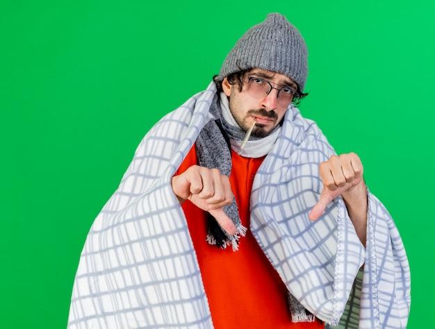 緑の壁に隔離された親指を下に表示している口の中で温度計を保持している格子縞に包まれた眼鏡の冬の帽子とスカーフを身に着けている弱い若い白人の病気の男