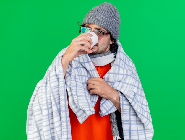 Weak young caucasian ill man wearing glasses winter hat and scarf wrapped in plaid grabbing plaid looking at side drinking cup of tea isolated on green background