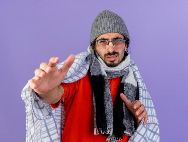 Debole giovane caucasico malato uomo con gli occhiali inverno cappello e sciarpa avvolto in un plaid guardando la telecamera allungando le mani verso la telecamera isolata su sfondo viola