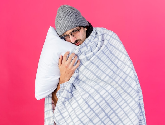 Debole giovane indoeuropeo uomo malato con gli occhiali cappello invernale avvolto in plaid tenendo il cuscino mettendo la testa su di esso guardando la telecamera isolata su sfondo cremisi