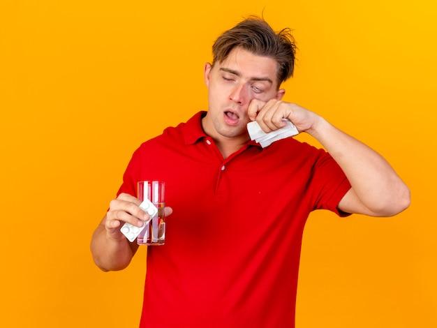 Debole giovane uomo malato biondo bello che tiene confezione di compresse mediche e bicchiere d'acqua con il tovagliolo che tocca il fronte isolato sulla parete arancione