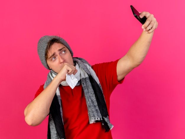 Weak young handsome blonde ill man wearing winter hat and scarf holding napkin keeping hand on mouth taking selfie isolated on crimson background