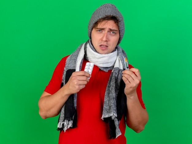 Debole giovane bell'uomo malato biondo che indossa cappello invernale e sciarpa che tiene il pacchetto di compresse mediche e siringa guardando la parte anteriore isolata sulla parete verde con lo spazio della copia