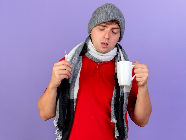 Debole giovane uomo malato biondo bello che indossa cappello invernale e sciarpa che tiene termometro e tazza isolato su sfondo viola