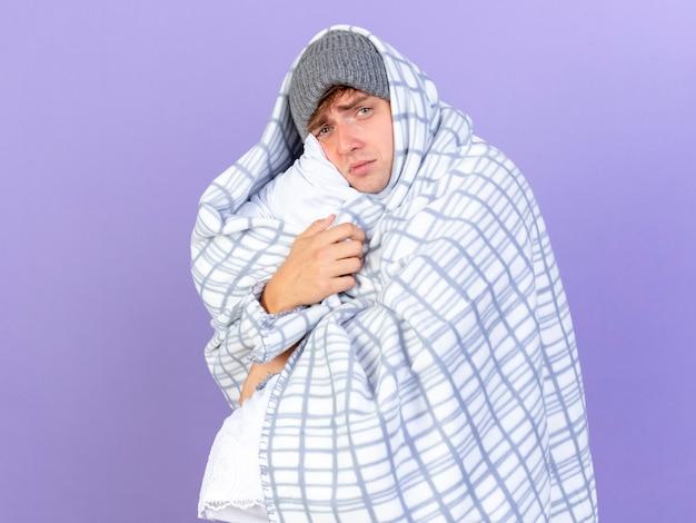 コピースペースで紫色の背景に分離されたカメラを見て枕を抱き締める縦断ビューに立っている冬の帽子をかぶって弱い若いハンサムな金髪の病気の男