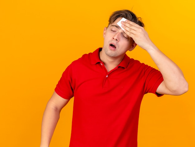 Weak young handsome blonde ill man wiping sweat with closed eyes isolated on orange background