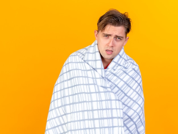 Weak young handsome blonde ill man wrapped in plaid looking at camera isolated on orange background with copy space