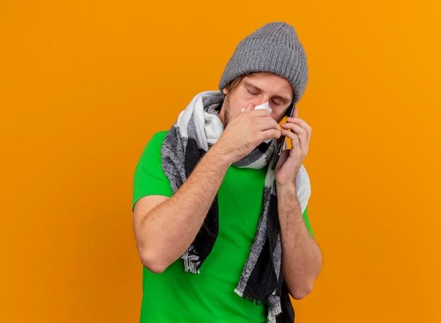 Debole giovane uomo malato bello che indossa cappello invernale e sciarpa parlando al telefono tenendo il tovagliolo asciugandosi il naso con gli occhi chiusi isolato sulla parete arancione