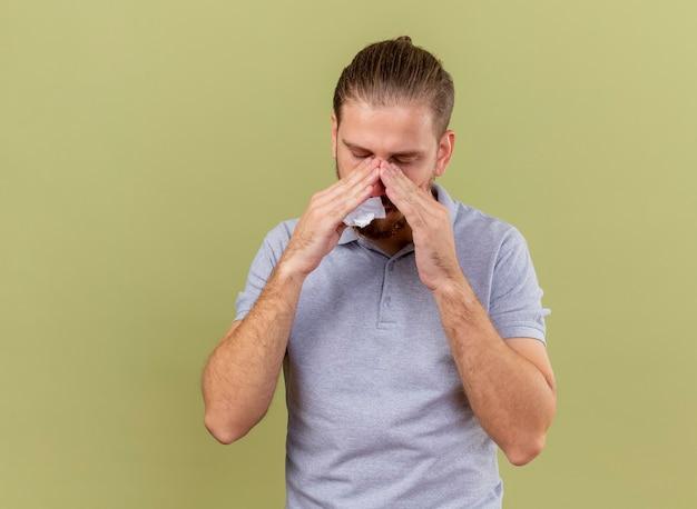 Слабый молодой красивый славянский больной мужчина держит салфетку, кладет руки на нос с закрытыми глазами, изолированными на оливково-зеленом фоне с копией пространства