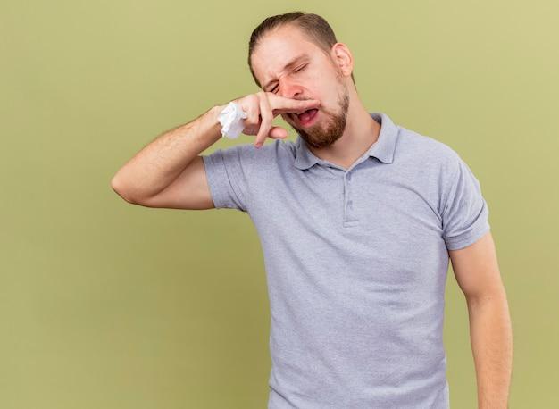 Слабый молодой красивый славянский больной мужчина держит салфетку, вытирая нос с закрытыми глазами, изолирован на оливково-зеленом фоне