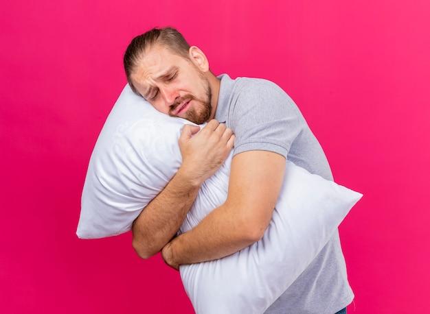Слабый молодой красивый славянский больной обнимает подушку, кладя на нее голову с закрытыми глазами, изолированными на малиновом фоне