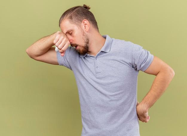 올리브 녹색 벽에 고립 된 닫힌 눈으로 코에 손을 넣어 냅킨을 들고 허리에 손을 유지 약한 젊은 잘 생긴 슬라브 병 남자