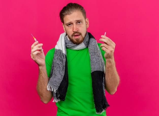 Weak young handsome slavic ill man wearing scarf holding syringe and ampoule looking at front isolated on pink wall with copy space