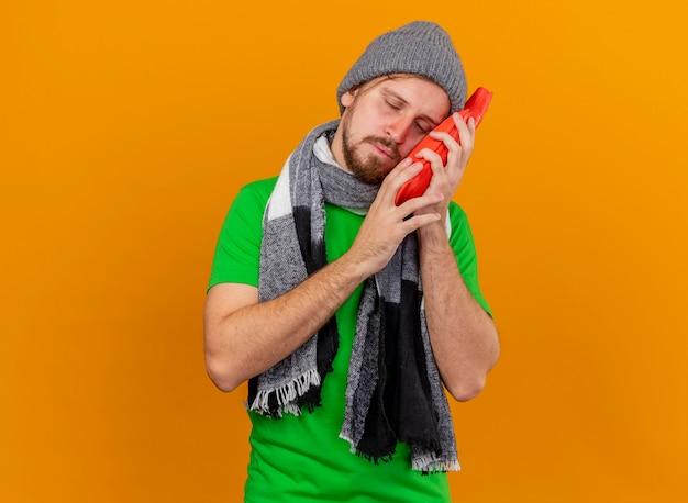 冬の帽子とスカーフを身に着けている弱い若いハンサムなスラブの病気の男は、コピースペースでオレンジ色の背景に分離された目を閉じて顔に触れる湯たんぽバッグを保持しています