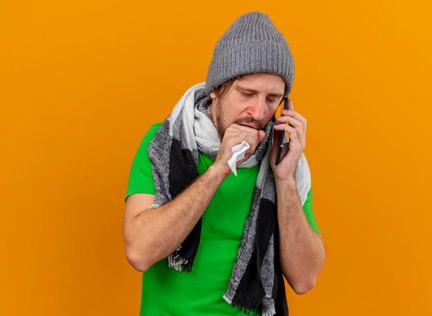 겨울 모자와 스카프를 착용하는 약한 젊은 잘 생긴 슬라브 병 남자가 복사 공간이 오렌지 배경에 고립 된 닫힌 눈으로 입 근처에 주먹을 유지하는 냅킨을 들고 전화로 이야기하는 스카프