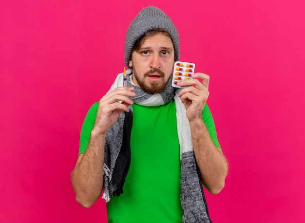 Weak young handsome slavic ill man wearing winter hat and scarf holding syringe and pack of capsules looking at front isolated on pink wall with copy space
