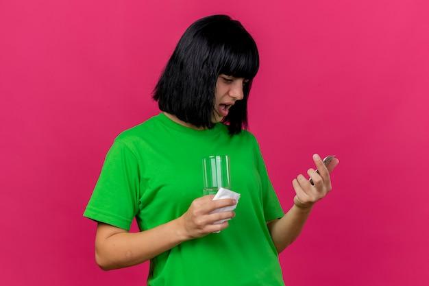 Debole giovane ragazza caucasica malata che tiene confezione di compresse tovagliolo e bicchiere d'acqua guardando compresse isolate su sfondo cremisi con spazio di copia