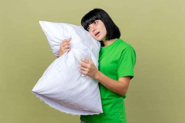 Debole giovane ragazza caucasica malata che tiene il cuscino guardando dritto con un bicchiere d'acqua in mano isolato sulla parete verde oliva con lo spazio della copia