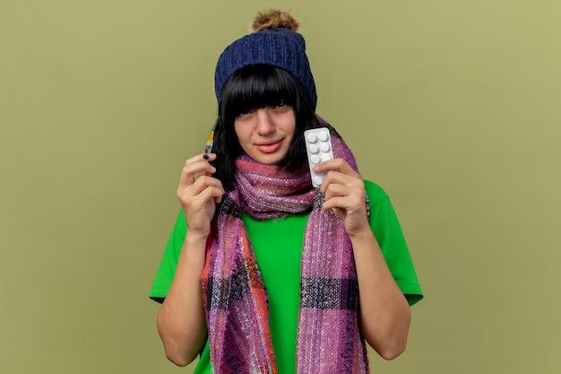 Debole giovane ragazza caucasica malata che indossa cappello invernale e sciarpa tenendo la siringa e il pacchetto di compresse medicali che guarda l'obbiettivo isolato su sfondo verde oliva con spazio di copia