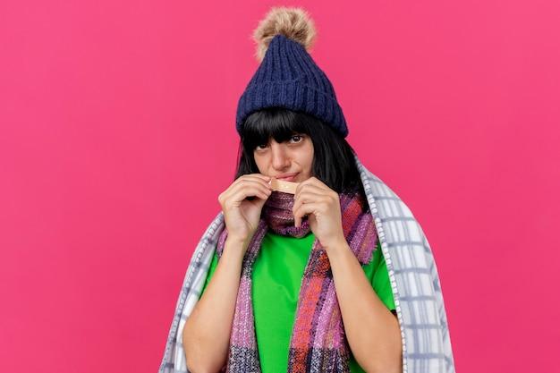 Debole giovane ragazza caucasica malata indossando cappello invernale e sciarpa avvolto in plaid guardando la telecamera tenendo intonaco vicino alla bocca isolato su sfondo cremisi con spazio di copia