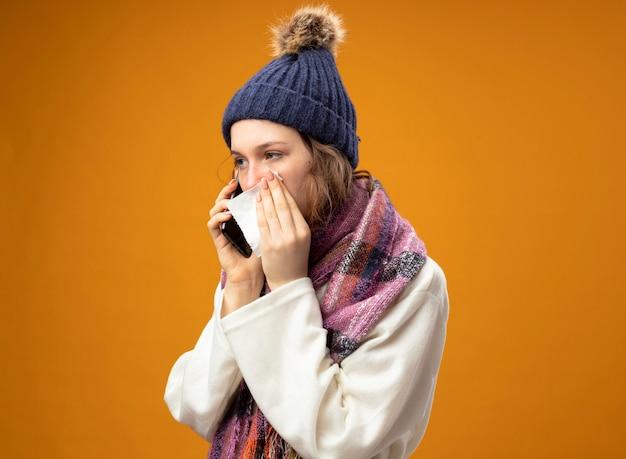 白いローブとスカーフと冬の帽子を身に着けている側を見ている弱い若い病気の女の子は、オレンジ色に分離されたナプキンで頬を拭く電話で話します