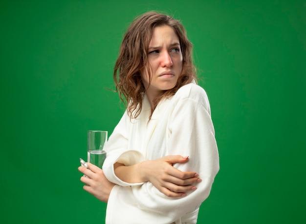 緑で隔離の手を交差する水のガラスを保持している白いローブを身に着けている側を見て弱い若い病気の女の子