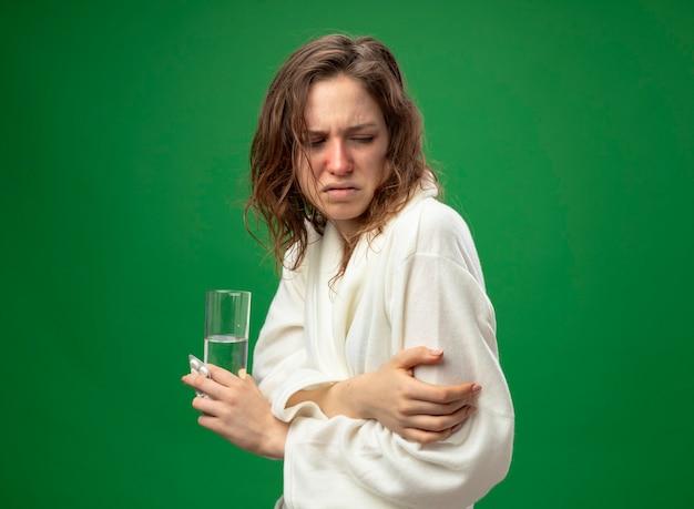 緑で隔離の手を交差する水のガラスを保持している白いローブを着て見下ろしている弱い若い病気の女の子
