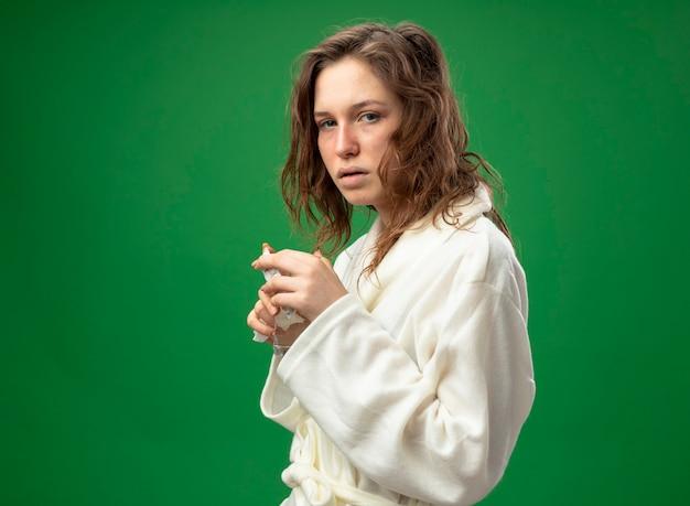 緑に分離された水のガラスを保持している白いローブを着てまっすぐ前を見て弱い若い病気の女の子