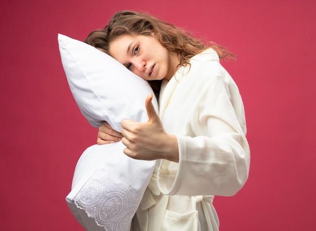 ピンクで隔離された親指を示す白いローブ抱き枕を身に着けているまっすぐ前を見て弱い若い病気の女の子