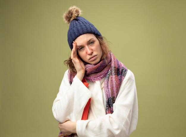 Слабая молодая больная девушка в белом халате и зимней шапке с шарфом держит мешок с горячей водой, положив руку на щеку, изолированную на оливково-зеленом