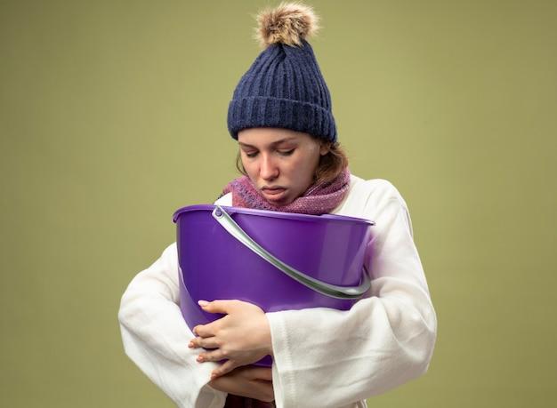 白いローブと冬の帽子を身に着けている弱い若い病気の女の子は、オリーブグリーンで吐き気を分離しているプラスチック製のバケツを保持しているスカーフ
