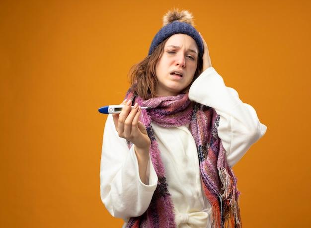 스카프를 들고 온도계를 들고 흰 가운과 겨울 모자를 쓰고 약한 어린 아픈 소녀가 머리에 손을 얹고 오렌지에 복사 공간이 있습니다.