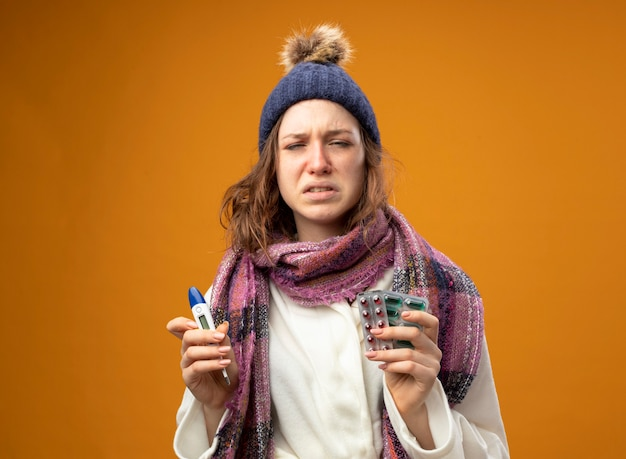 주황색 벽에 고립 된 약으로 온도계를 들고 스카프와 흰 가운과 겨울 모자를 쓰고 약한 어린 아픈 소녀