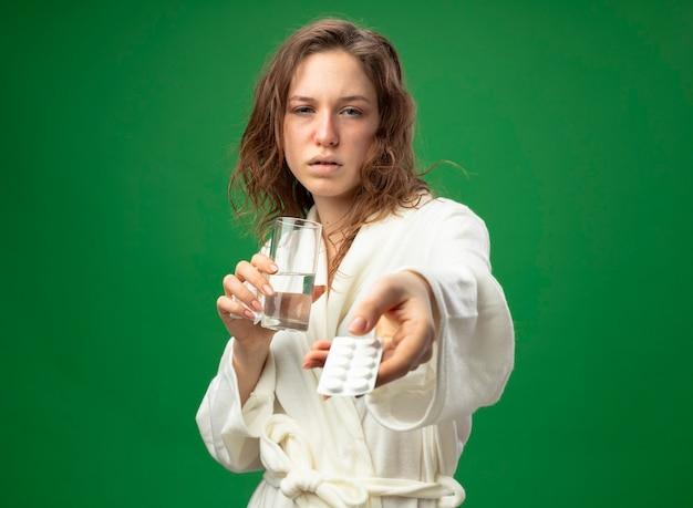 水のガラスを保持し、緑で隔離の丸薬を保持している白いローブを着ている弱い若い病気の女の子