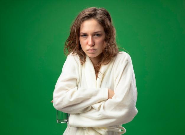 緑で隔離の冷たい手を凍らせる水のガラスを保持している白いローブを身に着けている弱い若い病気の女の子