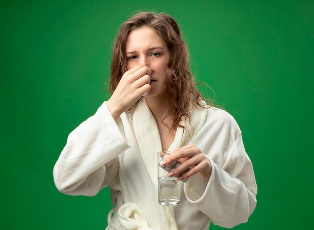 緑で隔離の丸薬とつかんだ鼻と水のガラスを保持している白いローブを着ている弱い若い病気の女の子
