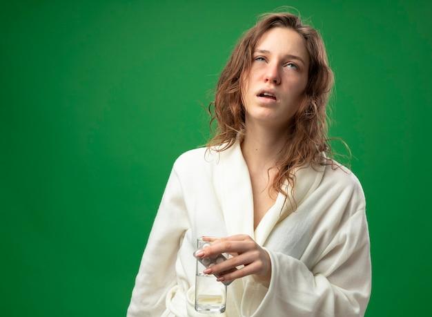 緑で隔離の丸薬と水のガラスを保持している白いローブを着ている弱い若い病気の女の子