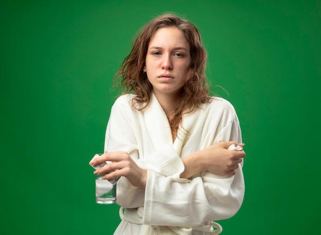 Debole giovane ragazza malata che indossa una veste bianca in possesso di bicchiere d'acqua attraversando le mani congelamento freddo isolato su verde
