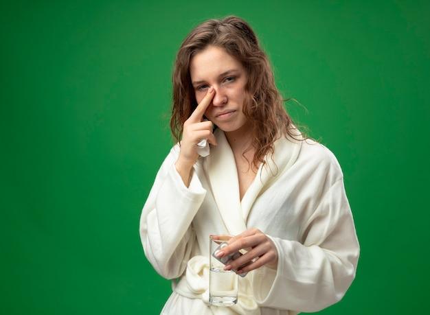 Debole giovane ragazza malata che indossa una veste bianca tenendo il bicchiere d'acqua con le pillole mettendo il dito sul naso isolato su verde con copia spazio