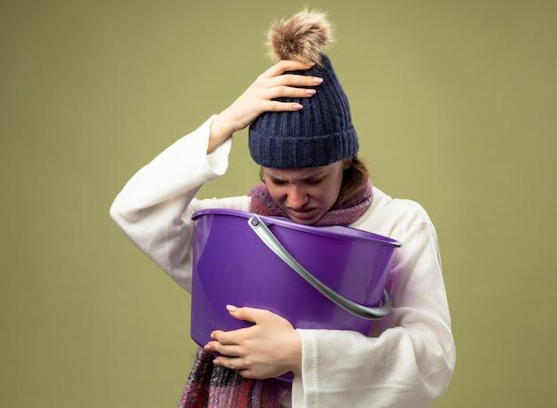 Debole giovane ragazza malata che indossa una veste bianca e cappello invernale con la sciarpa che tiene il secchio di plastica che ha nausea mettendo la mano sulla testa isolata su verde oliva