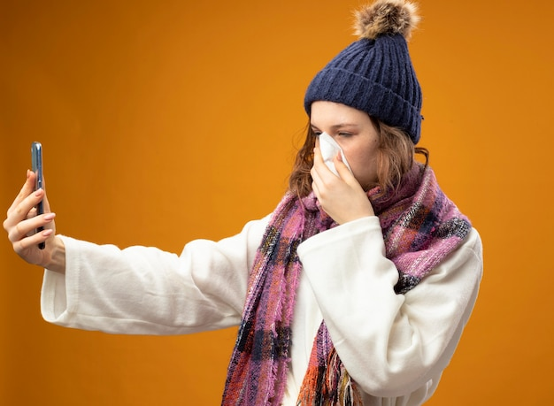 Weak young ill girl wearing white robe and winter hat with scarf take a selfie and wiping nose with napkin isolated on orange wall