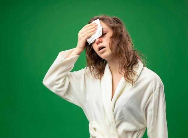 緑に分離されたナプキンで額を拭く白いローブを着ている弱い若い病気の女の子